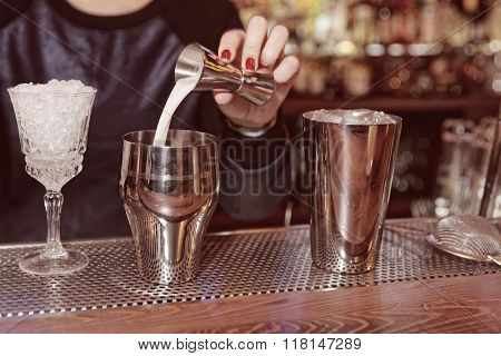 Bartender is adding milk to the metal shaker, toned