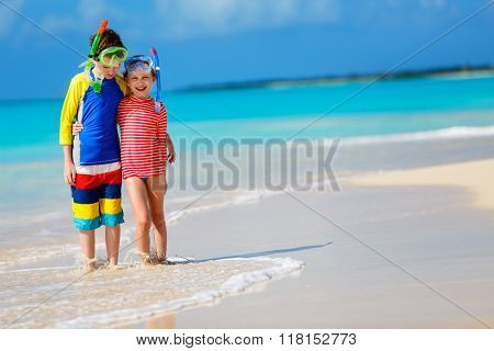 Little kids in rash guards for sun protection with snorkeling equipment on tropical beach during summer vacation