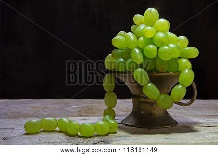 White Grapes Hanging Like A Necklace Out Of A Brass Bowl, Vintage Still Life