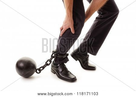 Ball and chain restraining a businessman as he tries to walk concept for business burden, willpower and determination