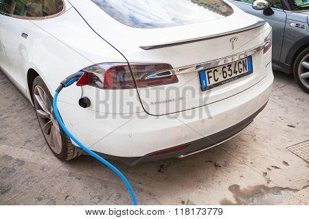 White Tesla Model S Car Charging At Recharging Station