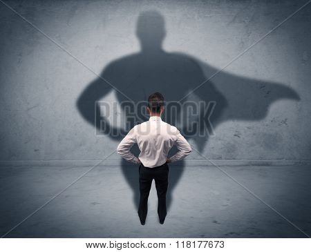 A confident young elegant salesman with briefcase facing a wall, looking at his superman shadow concept