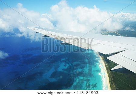 Wing Of An Airplane Flying Above The Clouds Over Tropical Island