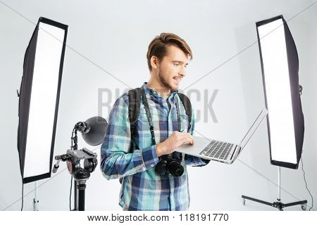 Happy male photographer using laptop computer in photo studio with eqipments