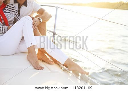 Couple Stting On Sailboat Deck In The Sea