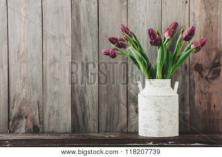 Bouquet of tulip flowers in vintage vase on the shelf over rough wooden background, rustic interior decor