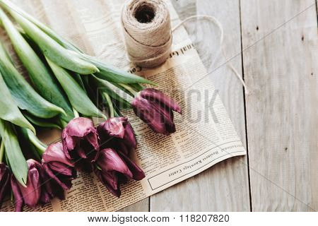 Spring tulips flowers wrapped in craft paper and twine on rough wooden table, selective focus, rustic eco style