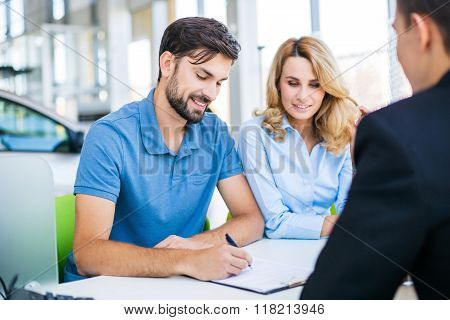 Photo of young male consultant and couple. Young woman and man buying new car in auto show. Signing of contract. Concept for car rental