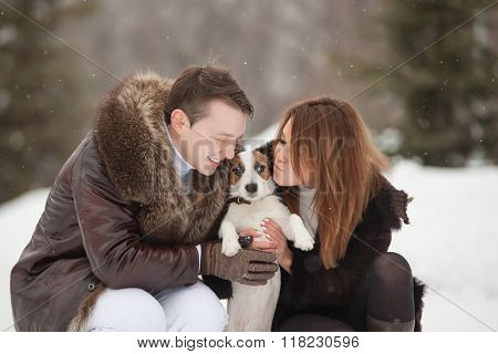 Happy couple and their dog Jack Russell Terrier at the winter park