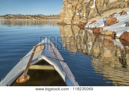canoe bow with a wooden paddle on a mountain lake with sandstone cliff - Horsetooth Reservoir in Fort Collins, Colorado