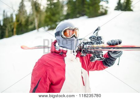 Young man holding ski at ski resort.Skier holding skis looking at the mountains.Side view of handsom