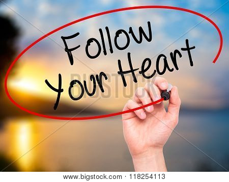 Man Hand Writing Follow Your Heart With Black Marker On Visual Screen