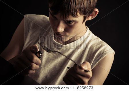 Male Teen Abusing Drugs With Spoon And Lighter