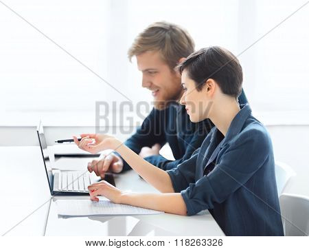 Business People Discussing Ideas At Meeting Using Laptop