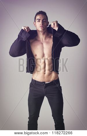 Handsome muscular young man taking off shirt