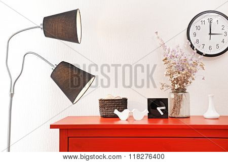 Room interior with red wooden commode, lamp and clock on light wall background