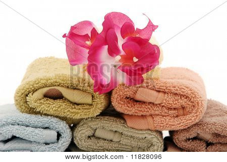 Stacked up spa bath towels and pink orchid
