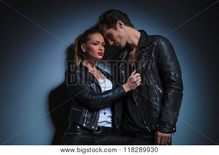 portrait of punk couple in leather posing in dark studio background. the man in starring at the woman while she is pulling his jacket and is lookin at the camera