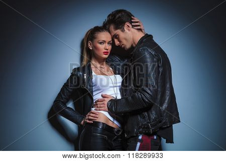 sexy man in leather jacket leans against his busty girlfriend that poses touching his head in studio