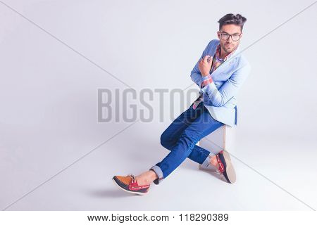 casual handsome man wearing glasses posing seated hith hands and legs crossed while looking away from the camera in studio background