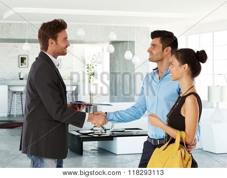 Young couple and real estate agent shaking hands, smiling. Side view.