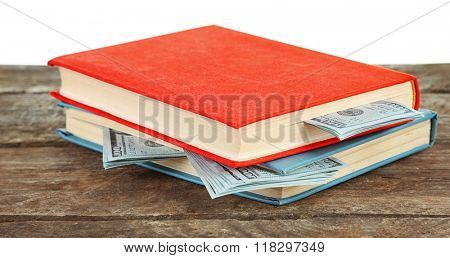 Books with nested dollar banknotes on white background. Stash of money