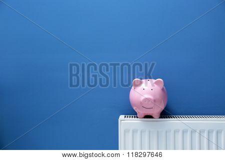 Piggy bank on radiator. Saving  heating in winter