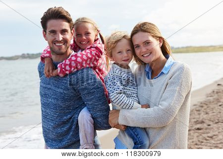 Portrait Of Family On Beach Vacation Walking By Sea