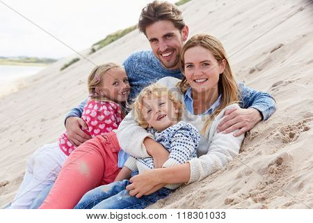 Portrait Of Family Lying In Sand Dunes Together