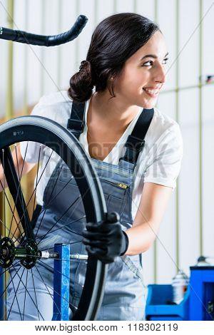 Woman bike mechanic working on bicycle
