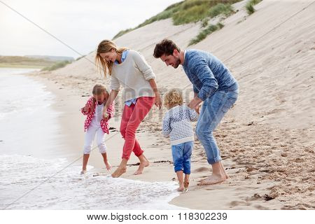 Family On Beach Vacation Playing By Sea