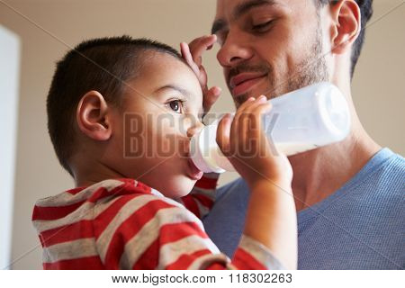Father Carrying Young Son As He Drinks Milk From Bottle