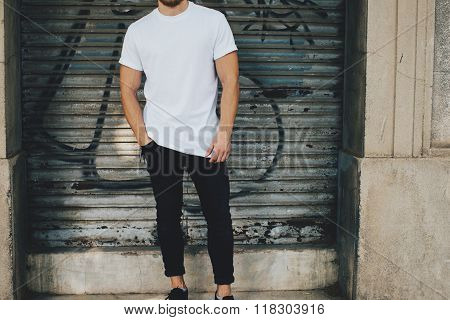 Bearded guy wearing white blank t-shirt and black jeans, standing opposite garage