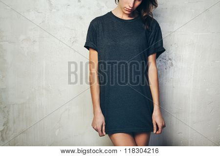 Young girl wearing blank black t-shirt. Concrete wall background. Horizontal