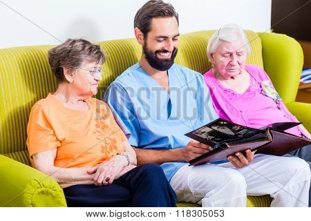 Geriatric nurse looking at pictures with seniors in nursery home
