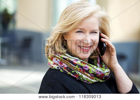 Mature beautiful blonde woman is calling on a cell phone, outdoors in spring