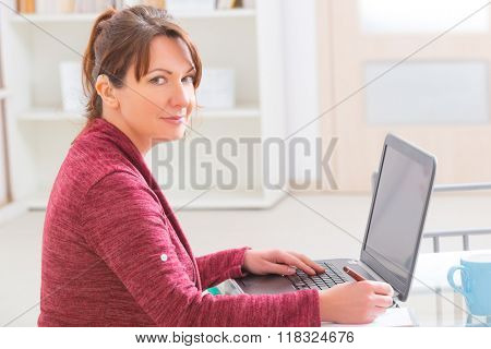 Hearing impaired woman working with laptop at home or office