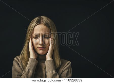 Portrait stressed sad young woman eyes closed hands touching head.