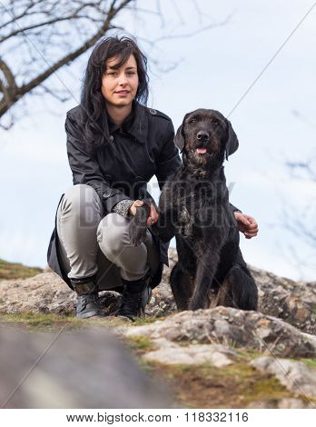 Beautiful girl with mutt black dog Amy on mountains, close-up.