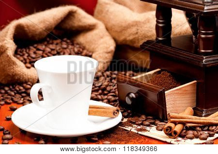 Coffee grinder and cup of coffee with spices on dark red background poster