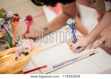 Hand of guests holding pens writing  on Signing books