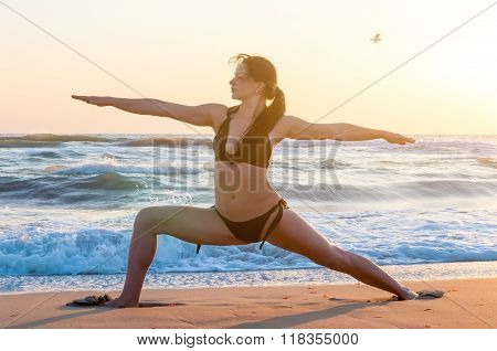 Silhouette of a young woman practicing yoga on the beach at sunrise. Sport, wellness concept