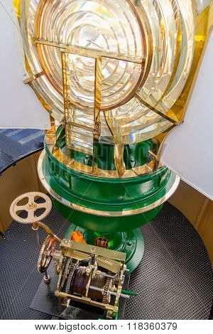 Lit Lighthouse light, with a view of the Fresnel optic system and the old clock mechanism at the bottom, still in use if the modern engine fails. Espichel Cape Lighthouse in Sesimbra, Portugal.