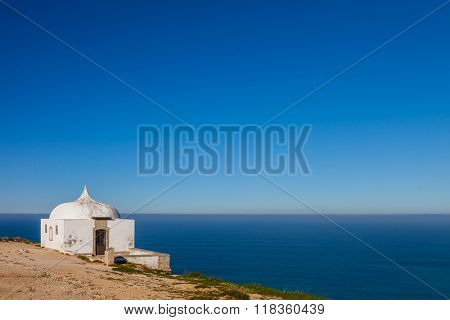 The remote Ermida da Memoria (Memory Hermitage) of the Nossa Senhora do Cabo Sanctuary, built on the edge of a cliff on Espichel Cape, with the Atlantic Ocean in background. Sesimbra, Portugal.