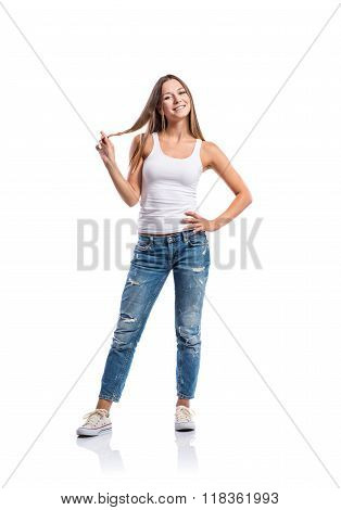 Woman in jeans and white singlet twirling hair,  isolated