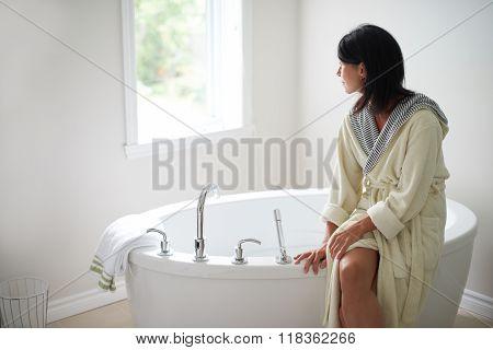 Serene mature woman sitting by a bathtub