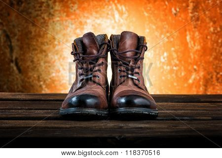 Men's brown winter boots isolated on rusty wooden background