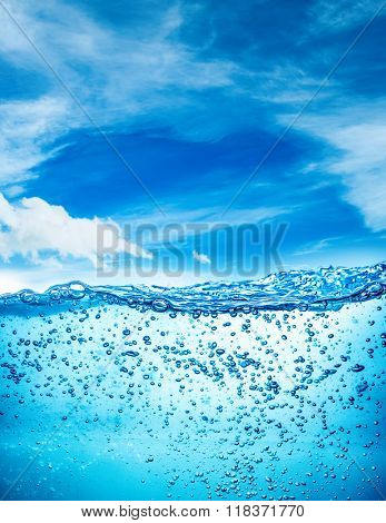 Many air bubbles in water close up, abstract water wave with bubbles on a background of blue sky