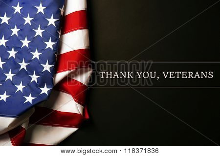 Text Thank A You, Veterans on black background near American flag poster