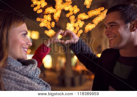 Happy joyful couple on Christmastime at street  with heart sign making by their hands